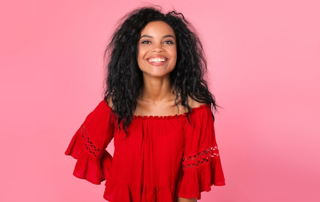 Prachtige afrikaanse etnische vrouw in een rode blouse poseert in semi-profiel, recht in de camera kijkend met een charmante glimlach