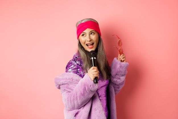 Prachtige aziatische senior vrouw die karaoke in microfoon zingt, lied uitvoert en er gelukkig uitziet, staande over roze achtergrond.