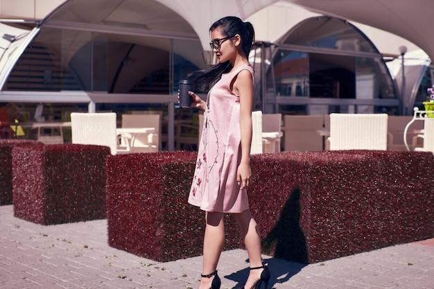 Prachtige aziatische vrouw in mode jurk op het terras van het restaurant