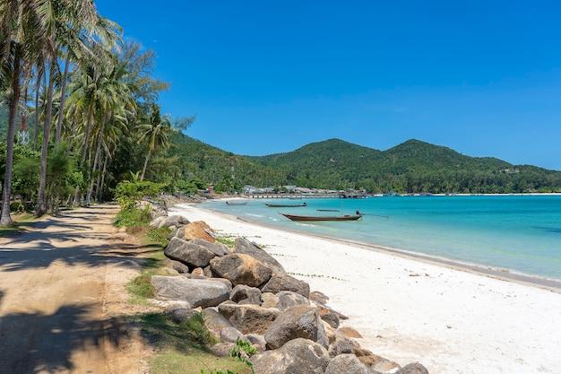 Prachtige baai met onverharde weg, blauw zeewater, kokospalmen en boten. tropisch zandstrand en zeewater op het eiland koh phangan, thailand