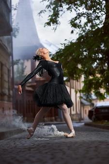 Prachtige ballerina in zwarte outfit die door de straten van de stad danst