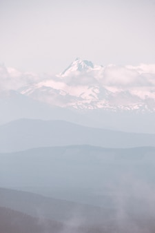 Prachtige berg bedekt met sneeuw en omgeven met wolken tijdens een mistig weer