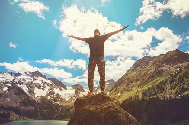 Prachtige bergen landschap met meer in altai bergen bergen en man op de top. mannelijke toerist met open armen. handen omhoog naar de hemel. het concept van vrijheid, wandelen en bergbeklimmen.