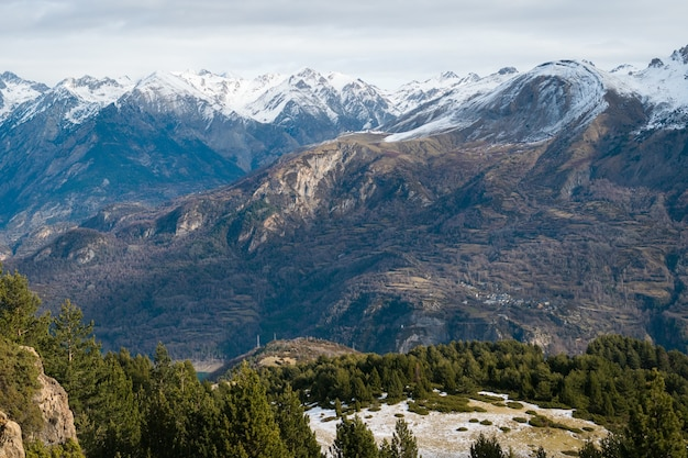 Prachtige bergketen bedekt met sneeuw gehuld in mist - ideaal voor een natuurlijk behang