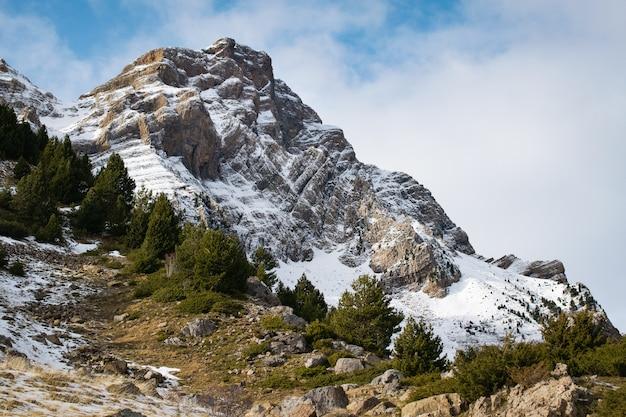 Prachtige bergketen bedekt met sneeuw gehuld in mist
