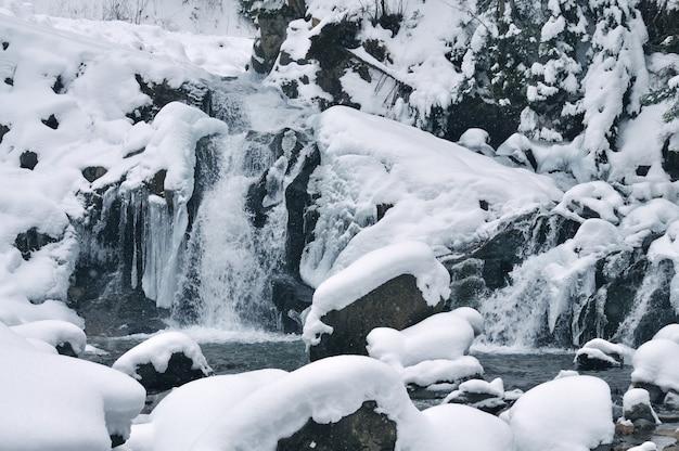 Prachtige besneeuwde waterval stroomt in de bergen