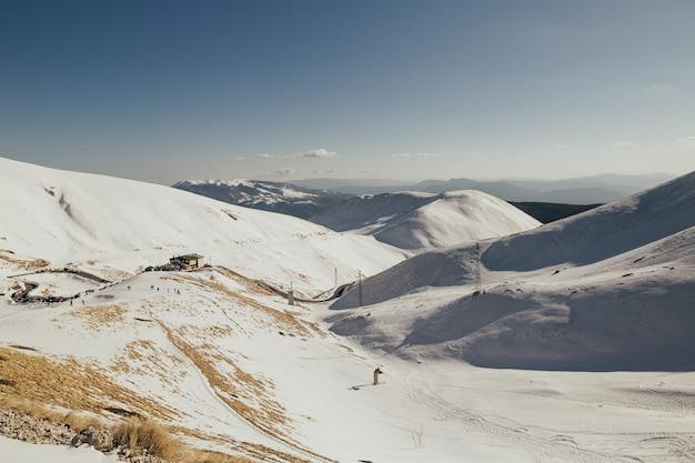 Prachtige besneeuwde winterlandschap panorama met skiresort, blauwe lucht, ski-tracks en skiërs.