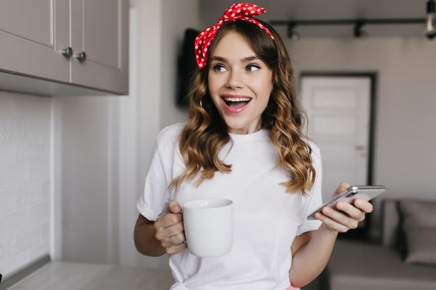 Prachtige blanke meisje telefoon houden en koffie drinken. indoor portret van vrij blij vrouw poseren met smartphone en kopje thee.