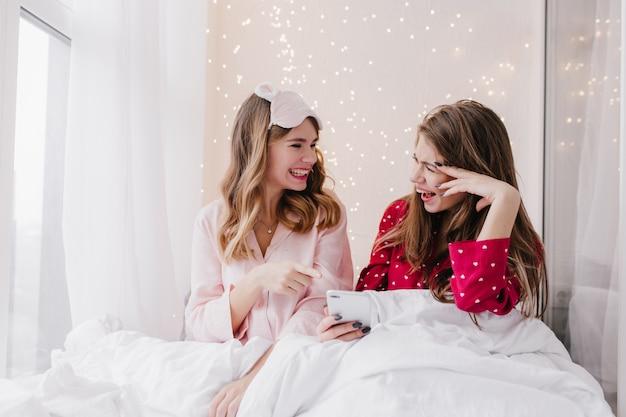 Prachtige blanke meisjes die een grapje maken terwijl ze 's ochtends vroeg poseren. binnenfoto van emotionele zusters in schattige pyjama's die elkaar met een glimlach aankijken.