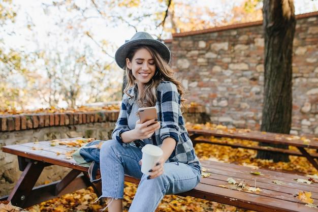Prachtige blanke vrouw draagt casual kleding sms-bericht in goede september-dag