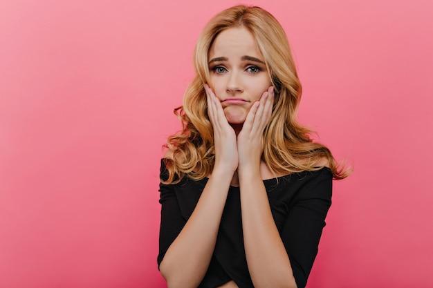 Prachtige blanke vrouw met grote ogen aanraken van haar gezicht met droevige uitdrukking. aantrekkelijk krullend meisje dat zich op roze muur bevindt.