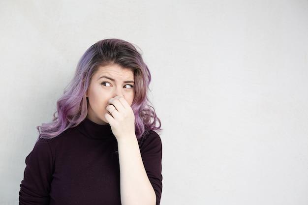 Prachtige blanke vrouw met paars haar adem inhouden met vingers op neus. walgelijk geurenconcept. ruimte voor tekst