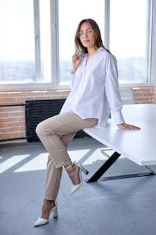 Prachtige blanke zakenvrouw in formele kleding zittend op een bureau in kantoor poseren
