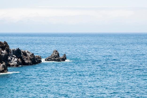 Prachtige blauwe zee met rotsen aan de kust