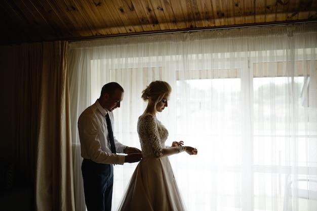 Prachtige, blonde bruid in een witte luxe jurk klaar voor de bruiloft Premium Foto