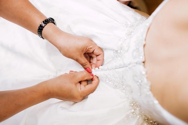Prachtige, blonde bruid in witte luxe jurk maakt zich klaar voor de bruiloft. ochtendvoorbereidingen. vrouw jurk aanzetten.