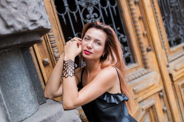 Prachtige blonde elegante vrouw in zwarte avondjurk poseren in de stad. rode lippen, rode haren, ongebruikelijke accessoires.