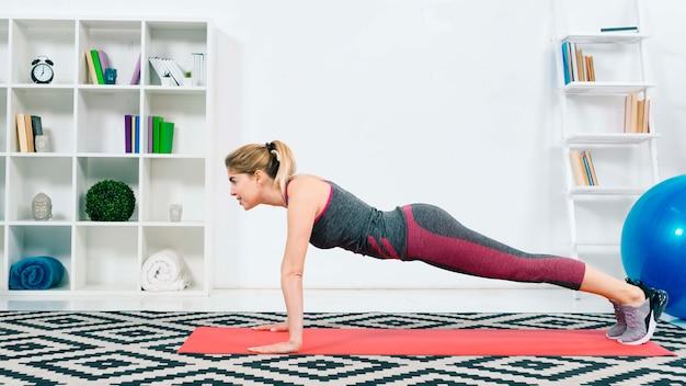Prachtige blonde jonge vrouw warming-up en doen push-up in de woonkamer