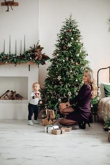 Prachtige blonde moeder en schattige zoon naast versierde kerstboom thuis. familiefeest.