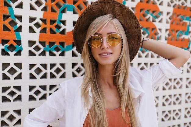Prachtige blonde vrouw die haar bruine hoed aanraakt tijdens het poseren in zomerverblijf. aanbiddelijke vrouw met lang kapsel dat zich dichtbij muur met glimlach bevindt.