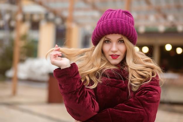 Prachtige blonde vrouw die warme winterkleren draagt, poserend op de achtergrond van lichten