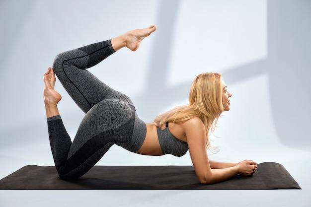 Prachtige blonde vrouw doet yoga op zwarte mat