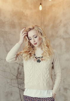 Prachtige blonde vrouw in beige trui