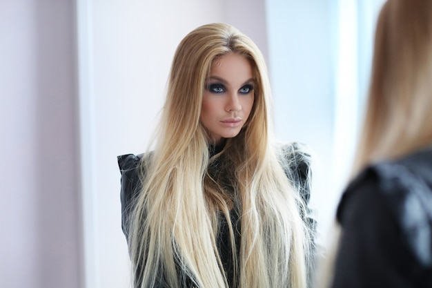 Prachtige blonde vrouw in leren jas