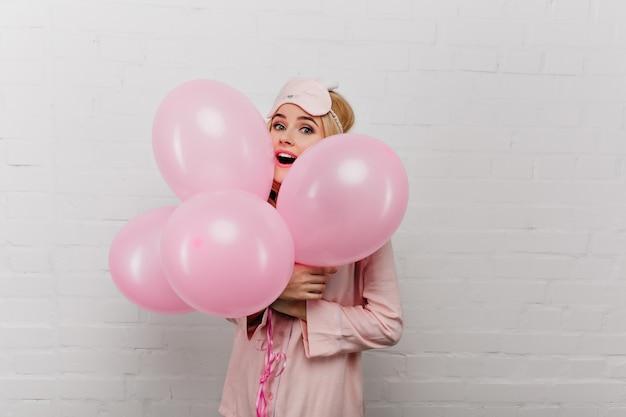 Prachtige blonde vrouw in roze pyjama ballonnen houden op witte muur. indoor portret van prachtige ontspannende feestvarken genieten van feest.