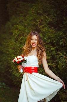 Prachtige blonde vrouw in witte korte jurk met rode strik poseren