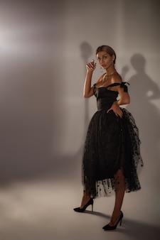 Prachtige blonde vrouw in zwarte cocktailjurk.