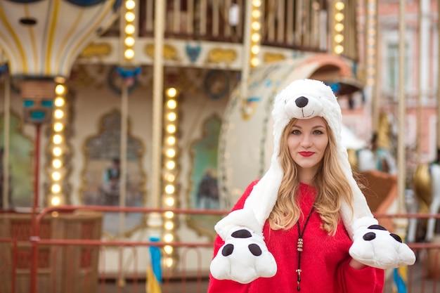 Prachtige blonde vrouw met een rode gebreide trui en grappige hoed, poserend op de achtergrond van een carrousel met verlichting