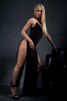 Prachtige blondine in een elegante avondjurk met een grote split