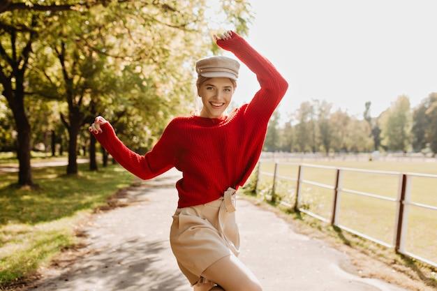 Prachtige blondine in trendy seizoenskleding die plezier heeft in het park. mooie jonge vrouw gelukkig gevoel buiten.