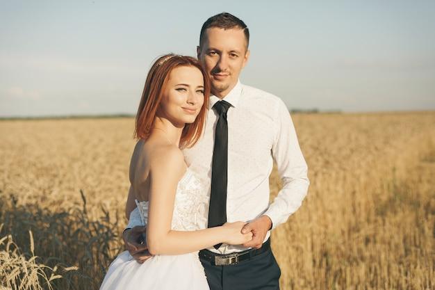 Prachtige bruid en bruidegom in een tarweveld. geluk en huwelijk