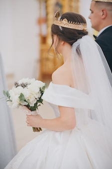 Prachtige bruid en bruidegom in gouden kronen. traditionele huwelijksceremonie jonggehuwden op oude kerk als achtergrond.