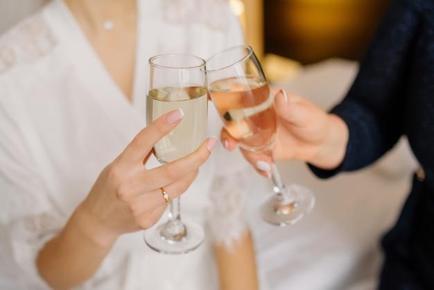 Prachtige bruid en bruidsmeisje roosteren champagne en plezier op huwelijksochtend. vrolijke jonge vriendinnen heffen een toast en gerinkelglazen. bruid ochtend. trouwdag