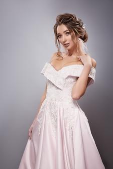 Prachtige bruid haar schouder in witte gekostumeerde jurk aan te raken