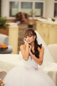 Prachtige bruid in trouwjurk in interieur