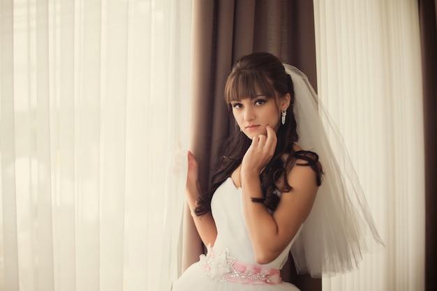 Prachtige bruid in trouwjurk in luxe interieur met diamanten juwelen