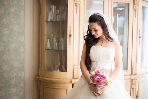 Prachtige bruid in trouwjurk in luxe interieur