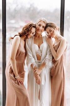 Prachtige bruid met de beste bruidsmeisjes vermaakt zich in de hotelkamer bij het grote raam.