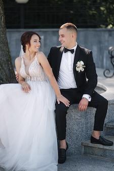 Prachtige bruid met stijlvolle bruidegom zit door grote boom in het park. gelukkig bruidspaar