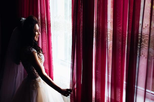 Prachtige bruid opent de gordijnen en kijkt uit het raam