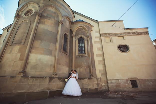 Prachtige bruidspaar geniet van een zonnige dag in de oude stad met architectuur