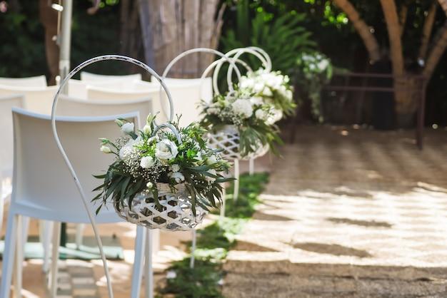 Prachtige bruiloft bloemstukken langs het gangpad