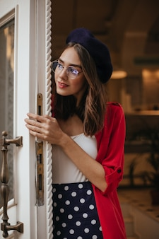 Prachtige brunette-haired vrouw in baret, polka dot rok, witte top, rood shirt en bril die de deur van het huis opent en overdag naar buiten kijkt