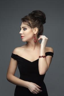 Prachtige brunette in een zwarte avondjurk met juwelen
