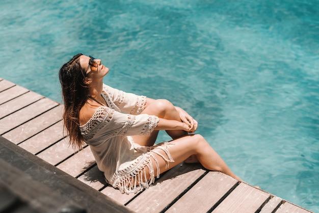 Prachtige brunette in zomerjurk een zonnebril zittend op dok