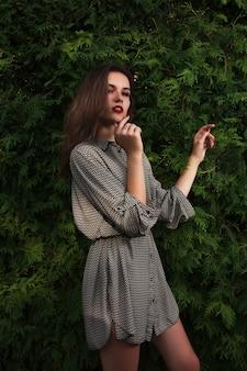 Prachtige brunette jonge model in casual shirt poseren op een groene thuja achtergrond